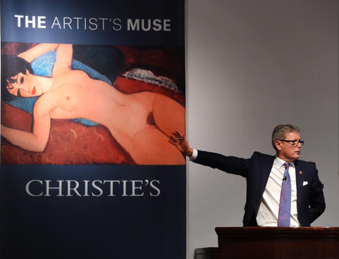 Auctioneer Jussi Pylkkanen gestures towards a picture of Amedeo Modigliani's 'Nu couche' during the 'Artist Muse: A Curated Evening Sale' November 9, 2015 at Christie's New York November 9, 2015. The painting sold for USD170,405,000.