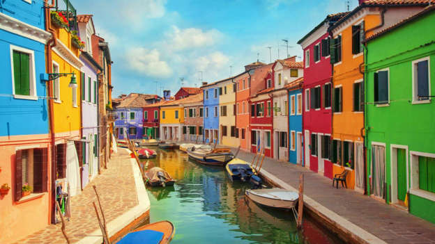 Like many of the colorful coastal towns on this list, legend has it that fishermen on the island of Burano began painting their homes in vibrant shades so they could see them in thick fog and avoid crashing into the shore after a voyage at sea. These days, residents must adhere to a strict color scheme by lodging an application with government before doing any renovations.