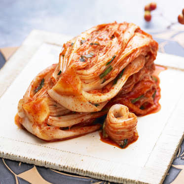 Kimchi is a spicy Korean condiment that's made with fermented cabbage and is a great source of vitamins A, B, and C. Because it's fermented (like sauerkraut), kimchi contains tons of those good probiotics that aid the body in digestion. A recent study in the Proceedings of the National Academy of Science found that maintaining healthy bacteria in your gut can improve gut lining, which in turn could help reduce fat mass and inflammation.<br><br>Look for kimchi in the refrigerated section at your grocery store and use it to flavor Korean-inspired dishes like dumplings or spicy beef stew.