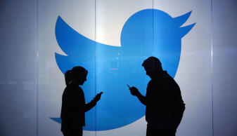 People are seen as silhouettes as they check mobile devices whilst standing against an illuminated wall bearing Twitter Inc.'s logo in London, U.K., on Tuesday, Jan. 5, 2016.