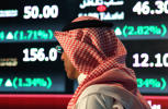 A Saudi man walks at the Tadawul Saudi Stock Exchange, in Riyadh, Saudi Arabia