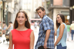 Disloyal man with his girlfriend looking at another girl.