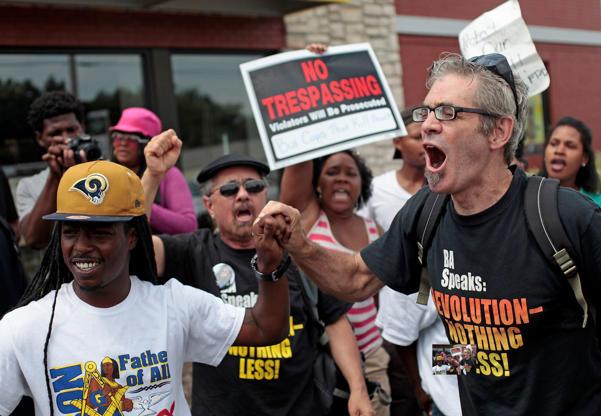 Demonstrators protesting Michael Brown's murder yell at police in Ferguson, Missouri, on August 18, 2014.