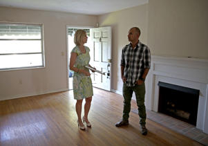 Denise Madan (L), a Real Estate agent with Re/Max, shows prospective buyer Juan Carlos Correa a home that is listed as a short sale as he shops for a house on April 22, 2014 in Coral Gables, Florida. Joe Raedle/Getty Images