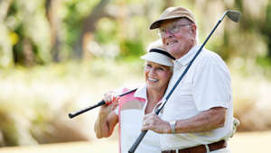 Senior couple, 70s, enjoying retirement on the golf course.