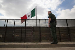 Border Patrol agent Jerry Conlin stands on the American side of the U.S.-Mexico border fence in San Ysidro, Calif.