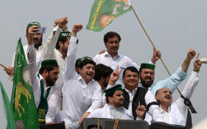 Pakistani Muslim League-Nawaz (PML-N) activists shout slogans as they start a journey towards Lahore to welcome former prime minister Nawaz Sharif on his return from London, in Peshawar on July 13, 2018. - Pakistan authorities locked down parts of Lahore on July 13 for the return from London of former premier Nawaz Sharif, who faces possible arrest and a 10-year prison sentence ahead of already tense elections his party insists are being rigged. (Photo by ABDUL MAJEED / AFP)        (Photo credit should read ABDUL MAJEED/AFP/Getty Images)