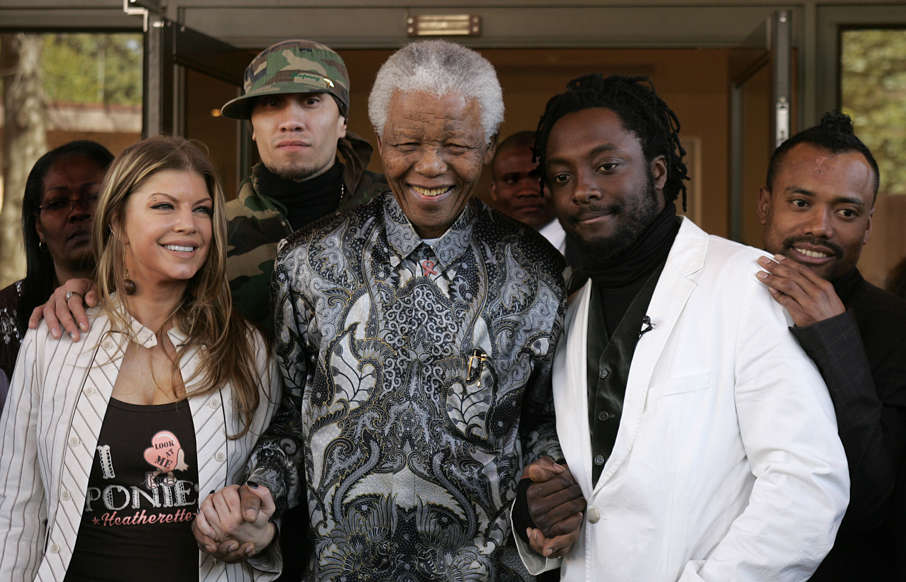 Slide 10 of 28: South African former president Nelson Mandela (C) poses for a picture with members of the Black Eyed Peas band from L to R: Fergie, Taboo, Will.I.Am and Apl.De.Ap in Johannesburg 29 May 2006 after making a courtesy call at Mandela's office. The Band is in South Africa for a benefit concert for Johannesburg's underprivileged people. AFP PHOTO / Alexander Joe (Photo credit should read ALEXANDER JOE/AFP/Getty Images)