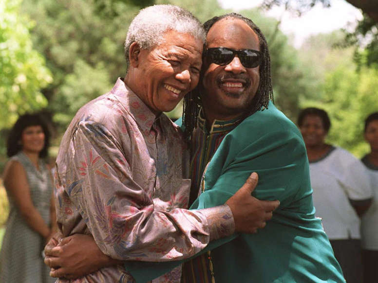Slide 11 of 28: South African President Nelson Mandela embraces American international pop-star Stevie Wonder (R) in Pretoria at the presidential residence 06 February. Mandela praised Wonder for his involvement in anti-apartheid activities when the African National Congress was still a banned organization in South Africa. AFP PHOTO (Photo credit should read WALTER DHLADHLA/AFP/Getty Images)