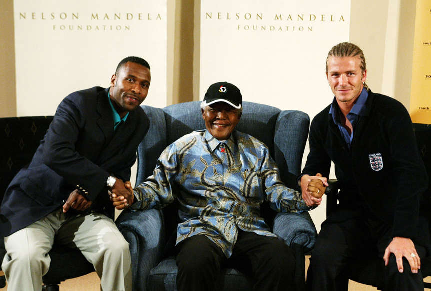 Slide 7 of 28: JOHANNESBURG - MAY 21: Lucas Radebe (L) and England captain David Beckham (R) pose with former South African President Nelson Mandela on May 21, 2003 at the Nelson Mandela Foundation in Houghton Johannesburg, South Africa. England will play a friendly match against South Africa in Durban on May 22, 2003. (Photo by Touchline/Getty Images)