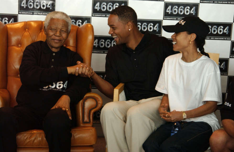 Slide 14 of 28: GEORGE, SOUTH AFRICA - MARCH 20: (EMBARGOED FOR PUBLICATION IN UK TABLOID NEWSPAPERS UNTIL 48 HOURS AFTER CREATE DATE AND TIME) (L-R) Nelson Mandela, actor Will Smith and his wife, Jada Pinkett-Smith, participate in, '46664 Celebrity Golf Tournament,' following yesterday's charity concert, '46664 South Africa,' at the Fancourt Hotel & Country Club on March 20, 2005 in George, South Africa. The event aims to raise awareness of the global HIV/AIDS pandemic, as well as raise funds for South Africa with proceeds going to the Nelson Mandela Foundation. The number '46664' represents Mandela's prison number during the 18 plus years he was imprisoned in South Africa's Robben Island jail. (Photo by Dave Benett/Getty Images)