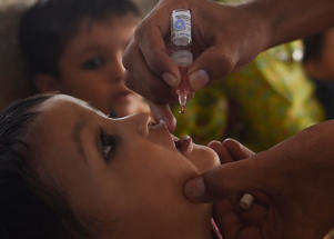 A Pakistani health worker administers polio vaccine drops to a child during a polio vaccination campaign at a railway station in Karachi on September 24, 2018. - Pakistan is one of only two countries in the world where polio remains endemic. (Photo by RIZWAN TABASSUM / AFP)        (Photo credit should read RIZWAN TABASSUM/AFP/Getty Images)