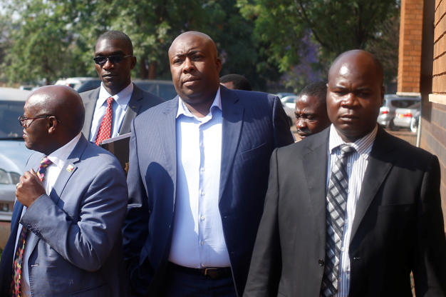 Slide 4 of 35: Former Zimbabwean minister Saviour Kasukuwere is escorted at the Magistrates court in Harare, Zimbabwe, September 25, 2018. REUTERS/Philimon Bulawayo