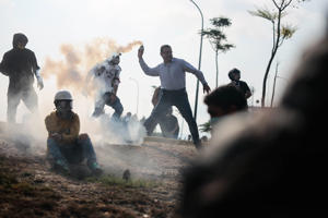"30 April 2019, Venezuela, Caracas: A man in civilian clothes throws a tear gas grenade around the self-proclaimed interim president Guaido near the air base La Carlota during a mission with soldiers. ""As interim president of Venezuela, as legitimate supreme commander of the armed forces, I call on all soldiers to join us,"" says the opposition leader on a highway. Photo: Rafael Hernandez/dpa (Photo by Rafael Hernandez/picture alliance via Getty Images)"