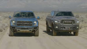 a truck driving down a dirt road: Raptor versus Power Wagon