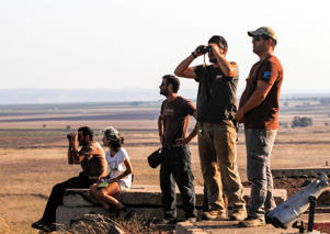 A picture taken on July 23, 2018 from the Israeli-annexed Golan Heights shows Israelis looking out across the border watching as warplanes backing a Syrian-government offensive carry out air strikes in the southwestern Syrian province of Daraa. - Israel has been on high alert since June 19, when Syrian government forces launched a Russia-backed offensive to retake Quneitra and Daraa and provinces, adjacent respectively to the Israeli-held section of the Golan and to Jordan, and have regained control of most of these two provinces through a combination of deadly bombardment and Moscow-brokered surrender deals. (Photo by JALAA MAREY / AFP)        (Photo credit should read JALAA MAREY/AFP/Getty Images)