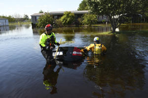 Joel Geary, left, and Ian Elliot, members of Colorado Task Force 1, search a car to make sure no one is inside after a driver lost control in the flood waters during the aftermath of Hurricane Florence on September 19, 2018 in Pembroke, North Carolina.