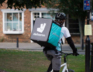 A cyclist from the increasingly popular take away delivery company Deliveroo speeding through city streets with a hot food delivery from take aways and restaurants to homes.