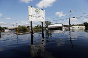 A sign commemorating the rebuilding of the town of Nichols, which was flooded two years earlier from Hurricane Matthew, stands in floodwaters in the aftermath of Hurricane Florence in Nichols, S.C., Friday, Sept. 21, 2018.