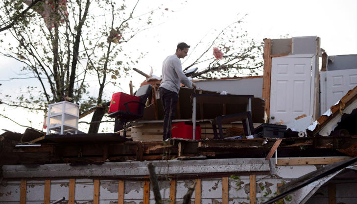 Slide 13 of 21: People collect personal effects from damaged homes following a tornado in Dunrobin, Ont. west of Ottawa on Sept. 21, 2018.