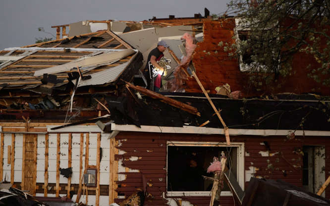 Slide 2 of 21: People collect personal effects from damaged homes following a tornado in Dunrobin, Ont. west of Ottawa on Sept. 21, 2018.