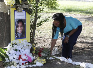 FILE - In this July 21, 2015 file photo, Jeanette Williams places a bouquet of roses at a memorial for Sandra Bland near Prairie View A&M University, in Prairie View, Texas. A state investigation of a white state trooper's actions in the arrest of Bland, a black motorist who later died in custody, found that the trooper, Brian Encinia, was rude toward Bland and failed to follow standard procedures in his handling of the woman. (AP Photo/Pat Sullivan, File)