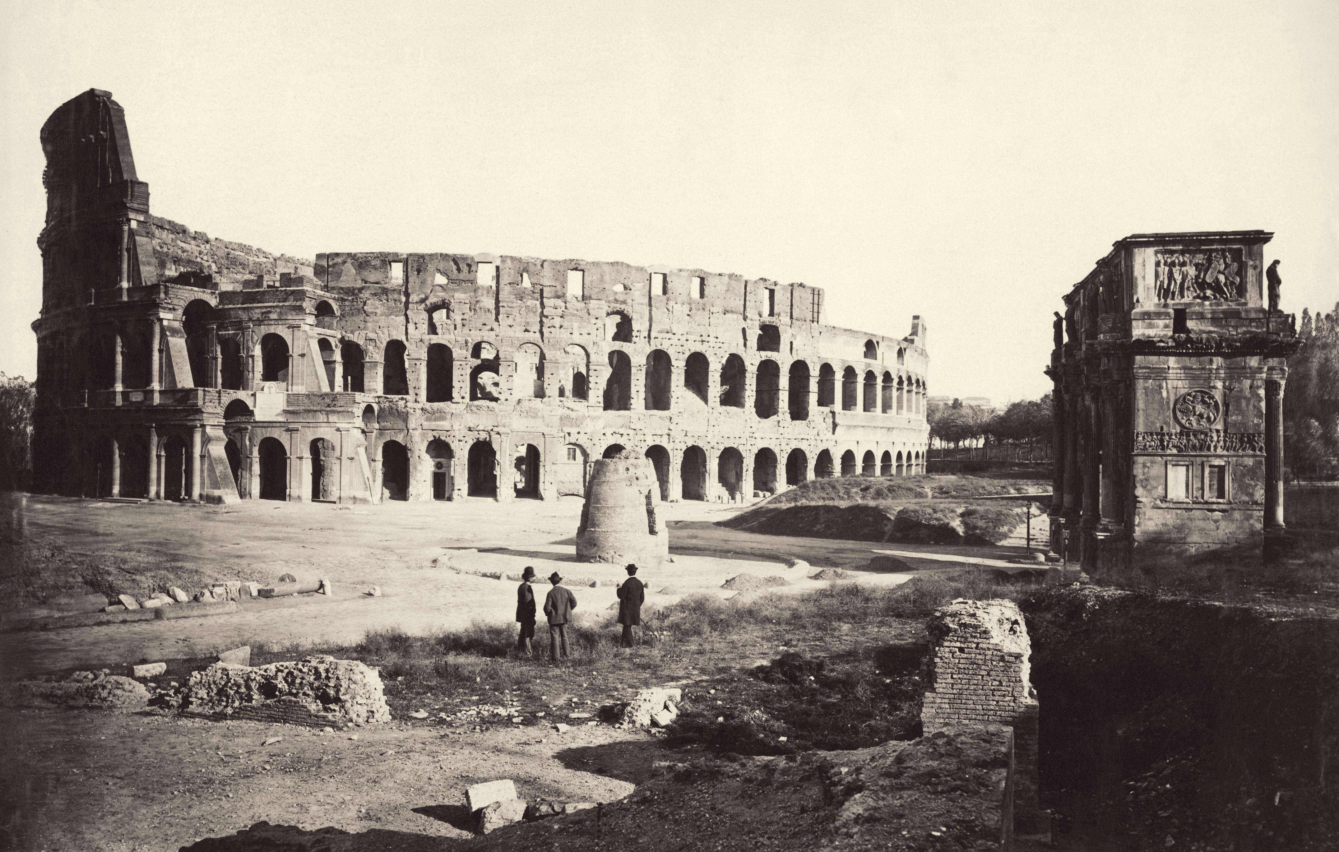 Slide 21 of 55: The Flavian Amphitheatre or Colosseum in Rome, with the Arch of Constantine on the right and Meta Sudans (a small conical brick fountain) in the centre, circa 1865. (Photo by Sean Sexton/Getty Images)