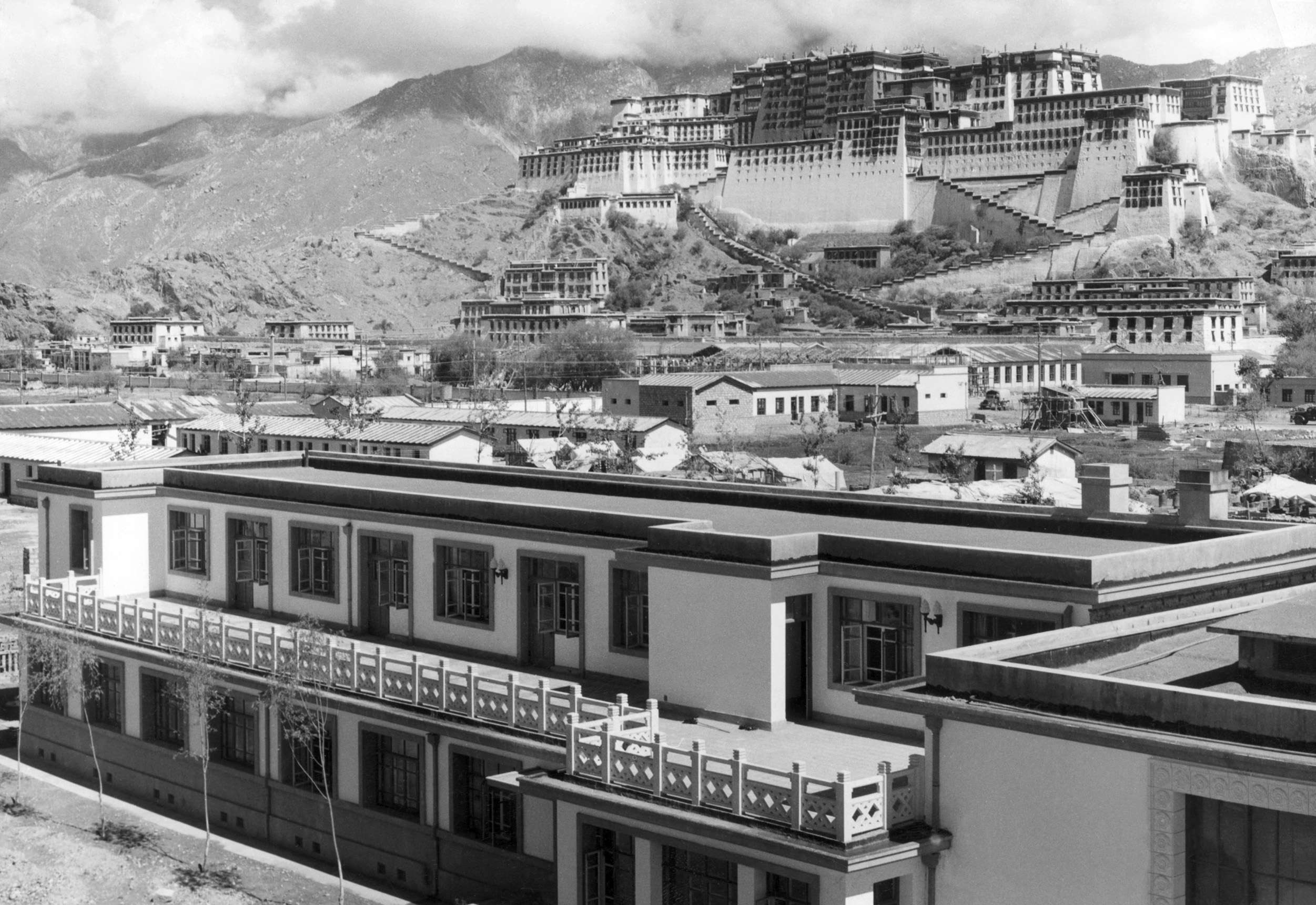 """Slide 19 of 55: Lhasa: A picture released by Chinese official news agency in August 1965 with a caption saying: """"New buildings are going up at the foot of the Potala Palace (in the background, the former home of the Dalai Lama) in Lhasa. The total floor space of new housing built in Lhasa since liberation 15 years ago has more than doubled the floor space of pre-liberation days"""". In March 1959, there was an unsuccessful armed uprising by Tibetans against Chinese rule. As a result, the Dalai Lama, the head of Tibet's Buddhist clergy and thus the region's spiritual leader, fled with some 100,000 supporters to northern India, where a government-in-exile was established. The Chinese ended the the former dominance of the lamas (Buddhist monks) and destroyed many monasteries. Tibet (Xizang), occupied in 1950 by Chinese Communist forces, became an """"Autonomous Region"""" of China in September 1965, but the majority of Tibetans have continued to regard the Dalai Lama as their """"god-king"""" and to resent the Chinese presence, leading to intermittent unrest. (Photo credit should read JU SHUI-CHU/AFP/Getty Images)"""