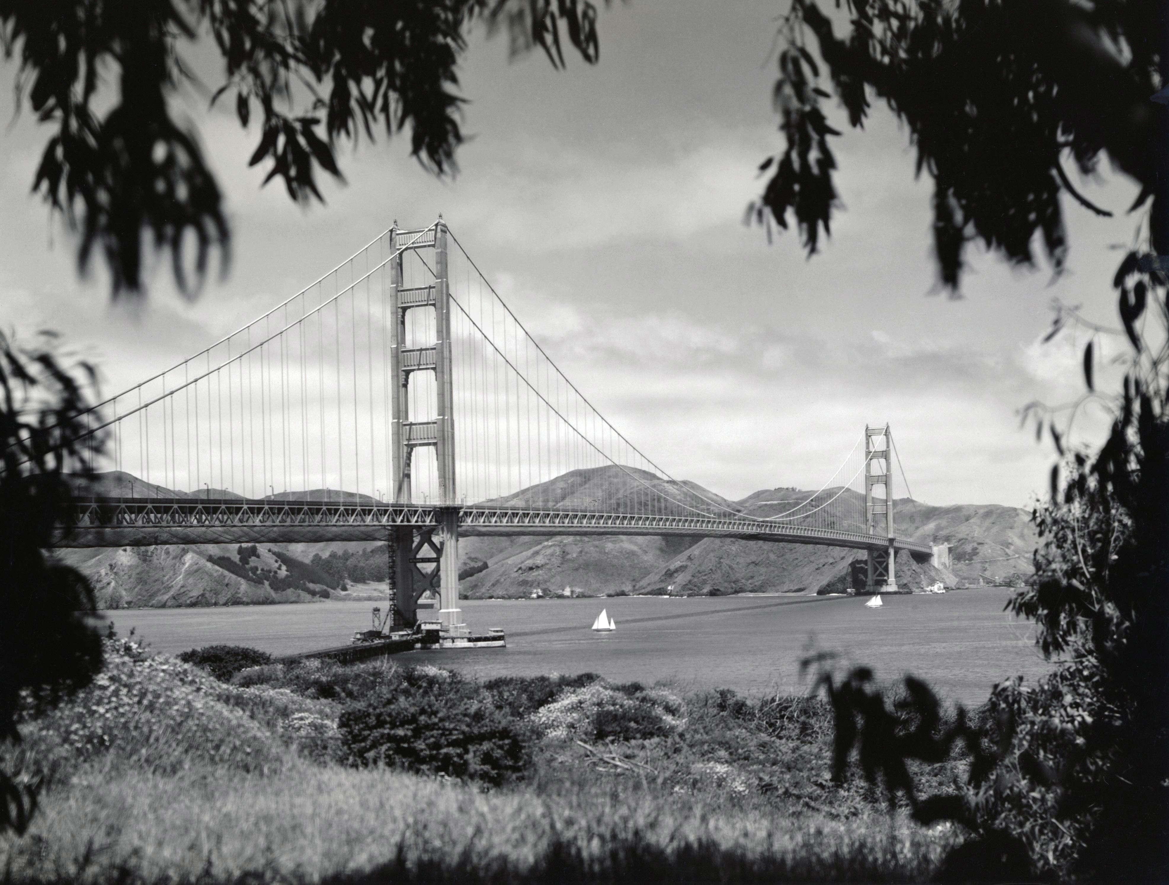 Slide 2 of 55: San Francisco, California: May, 1937 The nearly completed Golden Gate Bridge as seen from the Presidio with the Marin Headlands in the background. The workers' safety netting can still be seen hanging under the roadbed on parts of the bridge.