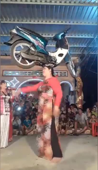 Woman dances with motorcycle on her head