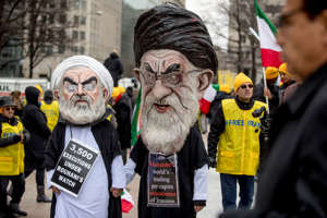 Two people dressed as Iranian President Hassan Rouhani, left, and Iran's supreme Leader Ayatollah Ali Khamenei, right, walk through Freedom Plaza during a Organization of Iranian-American Communities rally in Washington, Friday, March 8, 2019. (AP Photo/Andrew Harnik)
