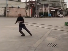 Old Chinese man works out with giant metal hula-hoop