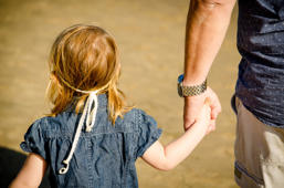 Little girl holding a male's hand. This could be her father, or a pedophile.