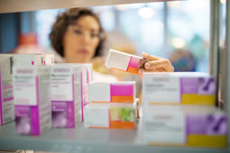 Female pharmacist checking medicines on rack. Chemist examining the medicines at drugstore. Focus on medicine boxes on the shelf.