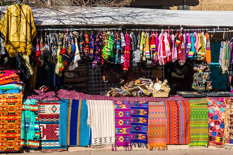 a bunch of items that are hanging on the wall: Santa Fe markets feature goods by local artisans, including jewelry, pottery, and other traditional wares.