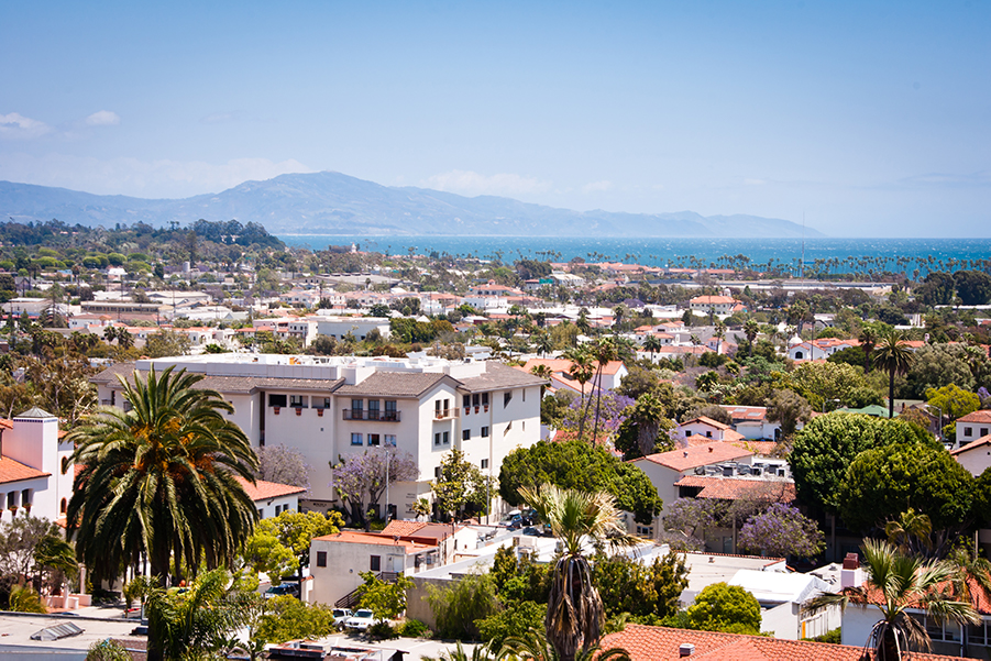 a large building with a mountain in the background: Visit Santa Barbara for design-forward accommodations, top-notch eats, and some of California's best wine.