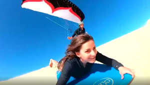 Sandboarder takes on paraglider in race down dune
