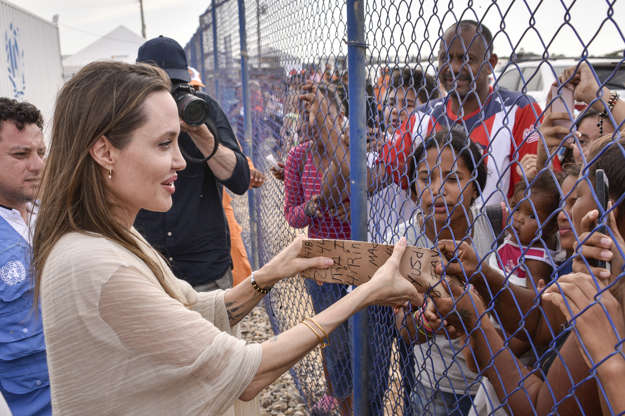 Slide 3 of 85: MAICAO, COLOMBIA - JUNE 08: United Nations High Commissioner for Refugees (UNCHR) Special Envoy Angelina Jolie greets people during her visit to a refugee camp in the border between Colombia and Venezuela on June 8, 2019 in Maicao, Colombia. UN and International Organization for Migration (IOM) announced yesterday that 4 million of Venezuelans have left their country since 2015 due to the social, political and economic crisis, which means they are of the single largest population groups displaced from their country globally. The camp in Maicao has 60 tents  which can accommodate up to 350 people. Due to high demand, UNHCR is considering an expansion to give shelter to 1,400 people. Colombia it the top host of Venezuelan migrants and refugees, accounting 1.3 million. (Photo by Guillermo Legaria/Getty Images)