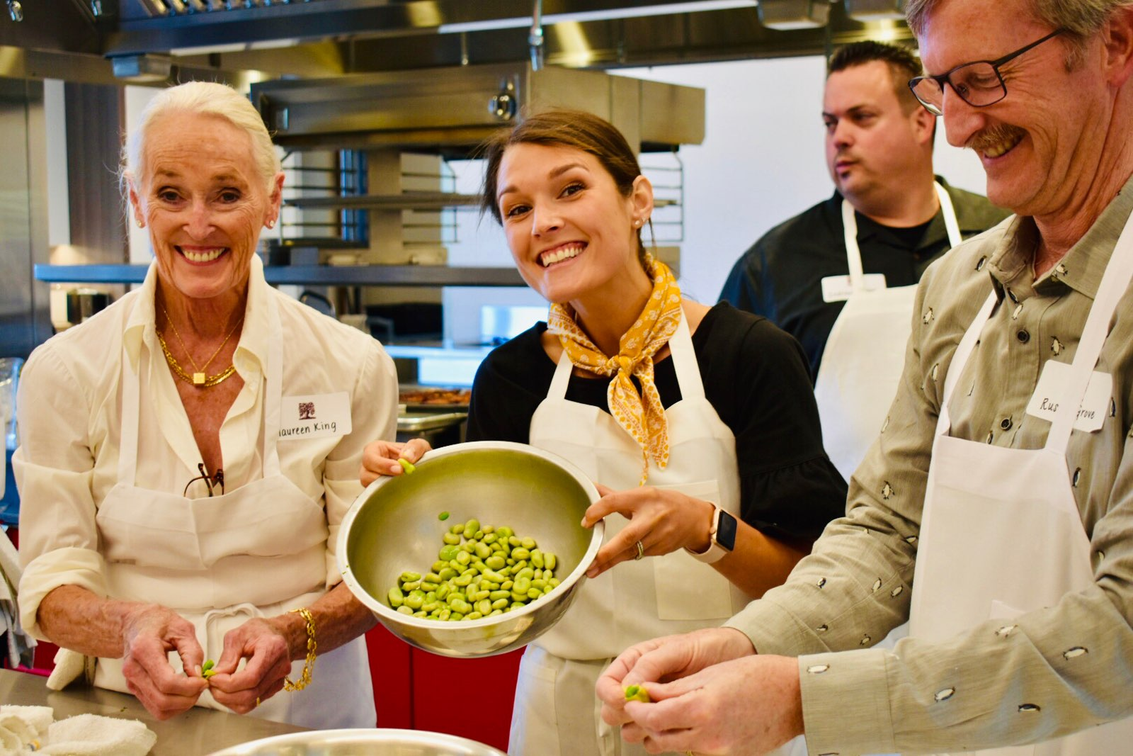 a man and woman cooking food in a bowl: Students at the new Biale cooking class show off fava beans, an ingredient for one of the recipes they learned for the day at CIA Copia.