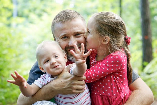 968c0b8f Devoted father hugging his son and daughter, enjoying the outdoor. Family  love and bonding
