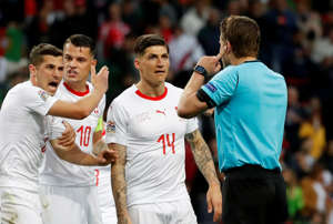 Soccer Football - UEFA Nations League Semi Final - Portugal v Switzerland - Estadio do Dragao, Porto, Portugal - June 5, 2019  Switzerland's Steven Zuber, Granit Xhaka and Remo Freuler remonstrate with referee Felix Brych as he consults VAR  REUTERS/Susana Vera