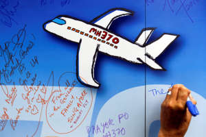 FILE - In this March 6, 2016, file photo, well wishes are written on a wall of hope during a remembrance event for the ill fated Malaysia Airlines Flight 370 in Kuala Lumpur, Malaysia . (AP Photo/Joshua Paul, File)