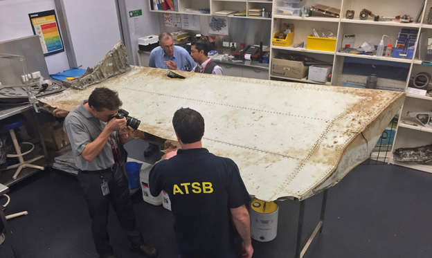In this photo released Friday, Sept. 16, 2016, by the Australian Transport Safety Bureau (ATSB), staff examine a piece of aircraft debris at their laboratory in Canberra, Australia, July. 20, 2016. The flap was found in June by residents on Pemba Island off the coast of Tanzania and officials had previously said it was highly likely to have come from flight MH370. An analysis by experts at the Australian Transport Safety Bureau, which is heading up the search for the plane, subsequently confirmed the part was indeed from the missing Boeing 777 aircraft, the agency said in a statement. (Photo/ATSB via AP)