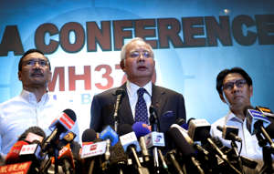 FILE - In this March 15, 2014, file photo, Malaysian Prime Minister Najib Razak, centre, Minister for Transport Hishamuddin Hussein, left, and director general of the Malaysian Department of Civil Aviation, Azharuddin Abdul Rahman, right, deliver a statement  (AP Photo/Wong Maye-E, File)