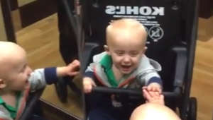 Baby sees three reflections in department store mirror
