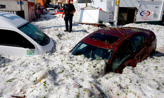 Slide 1 of 30: A policeman stands next to vehicles buried in hail in the eastern area of Guadalajara, Jalisco state, Mexico, on June 30, 2019. - The accumulation of hail in the streets of Guadalajara buried vehicles and damaged homes. (Photo by ULISES RUIZ / AFP)        (Photo credit should read ULISES RUIZ/AFP/Getty Images)