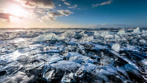 Large pieces of ice, sparkling like diamonds, on a black sand beach near Vatnajökull glacier with the sun low above the horizon.