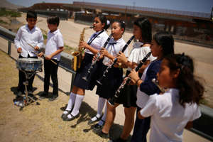 Young musicians perform near the border between the U.S. and Mexico to promote an upcoming concert to raise awareness around the plight of refugees, in Ciudad Juarez, Mexico June 21, 2019. REUTERS/Jose Luis Gonzalez - RC16F7A85B80