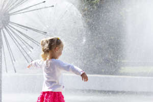 Little girl standing near the dandelion fountain with open hands.