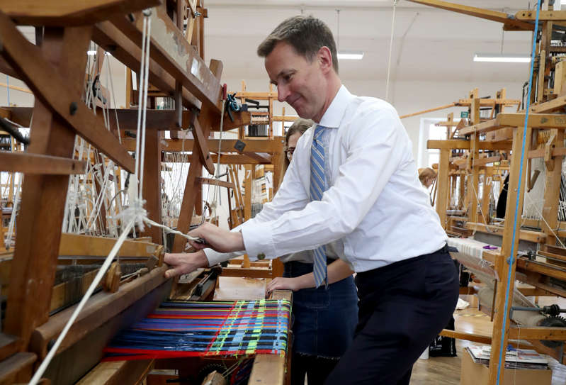 Foreign Secretary Jeremy Hunt operates a weaving loom during a visit to the School of Textiles and Design at the Heriot Watt University campus in Galashiels. (Photo by Jane Barlow/PA Images via Getty Images)